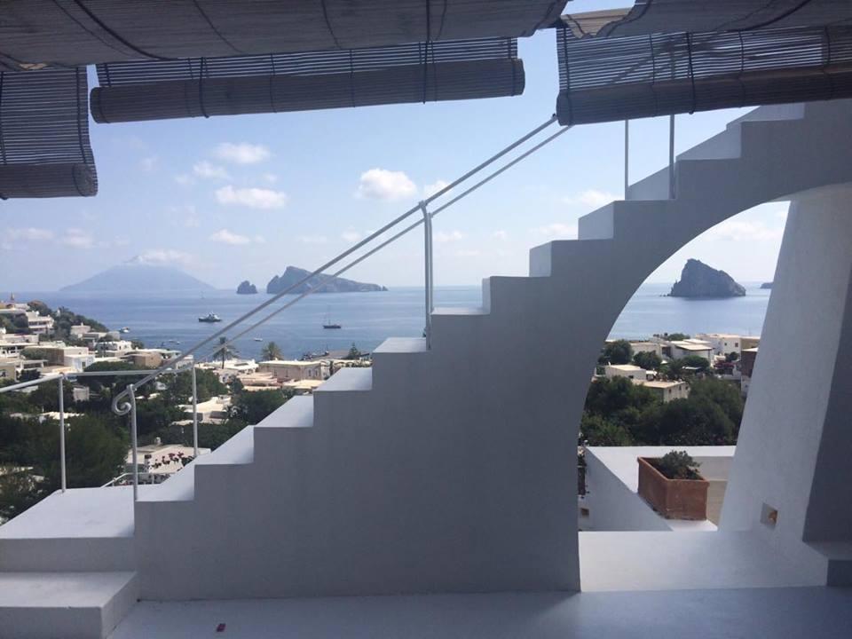 La terrazza della colazione, archi e scale incorniciano il panorama.