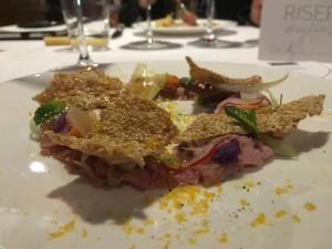 il Prosciutto di agnello al forno con tuorlo d'uovo affumicato, insalatina di stagione con patate viole, puntarelle, conserva di cipolla di Giarratana e cialdine di cuturro